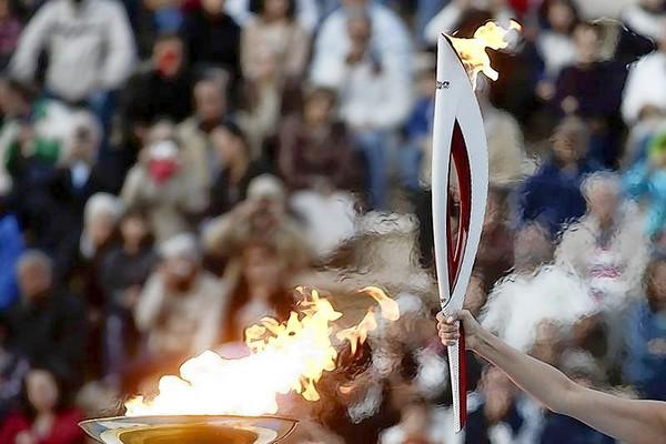 Greek actress Ino Menegaki, playing the role of high priestess, raises an Olympic torch of the Sochi 2014 Winter Games during a handover ceremony at the Panathenean stadium in Athens.