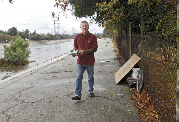 Ascencia's outreach case manager David Broadway left a note for a homeless man who was not with his belongings on the banks of the Los Angeles River at Bette Davis Park near the Glendale, Los Angeles border on a cold, rainy morning on Thursday, Nov. 21, 2013. Ascencia helps homeless find housing.