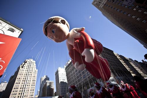 The Elf on a Shelf balloon floats above the street during the Macy's Thanksgiving Day Parade.