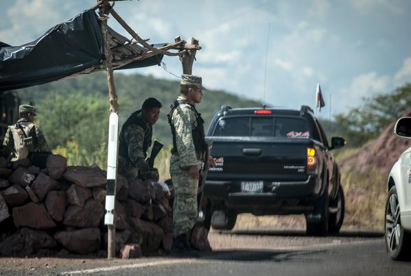 In this file photo from Nov. 5, 2013, Mexican soldiers stand at a checkpoint in the town of Tepalcatepec, in the state of Michoacan, Mexico.