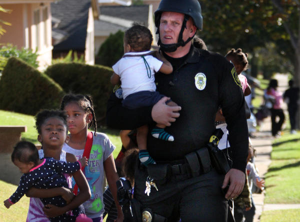 Inglewood police officer Joey Zeller leads children to safety from the neighborhood where two other police officers were injured during a hostage standoff.