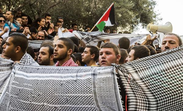 Supporters and relatives of Arab Israelis jailed by an Israeli court Thursday hold keffiyehs, the traditional Arab head dress, outside the court in the coastal city of Haifa. The defendants were convicted in connection with the killing of a far-right soldier in 2005.