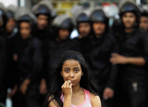 A female activist is pictured in front of riot police in downtown Cairo on Tuesday during a protest against a new law restricting demonstrations. Egyptian police broke out their batons and beat protesters, groped female demonstrators and detained at least 60 people.