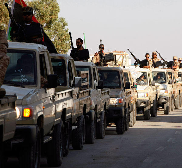 Members of the Libyan army force move towards the city of Bani Walid from, their headquarters in Tripoli October 18, 2012.