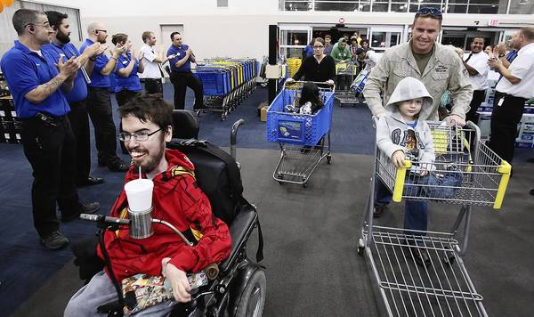 Best Buy employees in their blue shirts applaud as Phillip Parris, left, is the first in line to lead other shoppers into the store during an early opening for Black Friday shoppers at the Best Buy in Altamonte Springs on Thursday. (Stephen M. Dowell/Orlando Sentinel)
