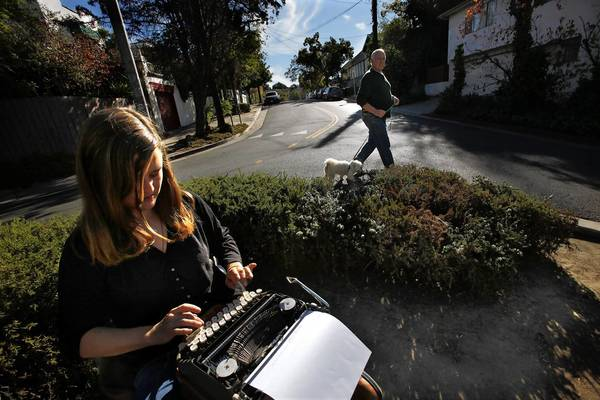 Stacy Elaine Dacheux, a writer and artist, sits at a small roundabout in Echo Park, typing on her vintage typewriter, as her neighbor Gene Novak walks his dog Coco up to see her.