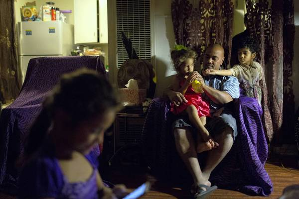 After church, Saia Holani sits with two of his children, 3-year-old Ana and 4-year-old Kaho, right, in the family's apartment in Inglewood. Katisha, 6, sits nearby.