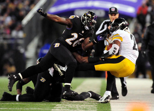 Steelers running back Le'Veon Bell gets knocked out of bounds by Ravens safety Matt Elam.