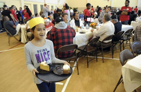 Aranza Morales, 9, of Tamarac, serves cheesecake at the Salvation Army Thanksgiving Feast Thursday in Fort Lauderdale. The Salvation Army and The Cheesecake Factory have held the feast for 14 years and this year served more than 500 meals.