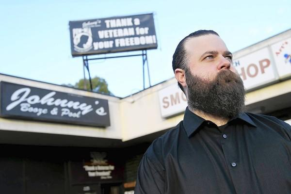 Johnny Kresimir in front of his bar in Huntington Beach, which the city cited for having an unpermitted rooftop sign.