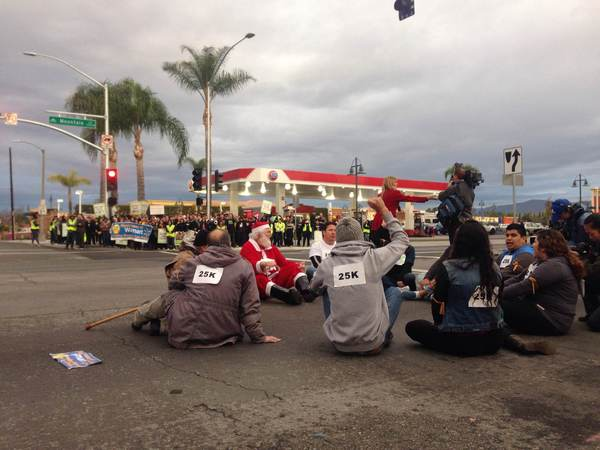Dozens of protesters chant outside the Wal-Mart store in Ontario early Friday morning, including a few who sat in the intersection of Mountain Avenue and 5th Street. They were demanding better wages and improved working conditions.