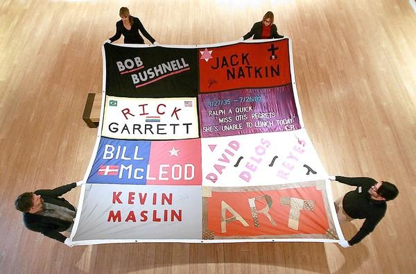 Staff members hold a panel from the AIDS Memorial Quilt that will go on display at the Laguna Art Museum.