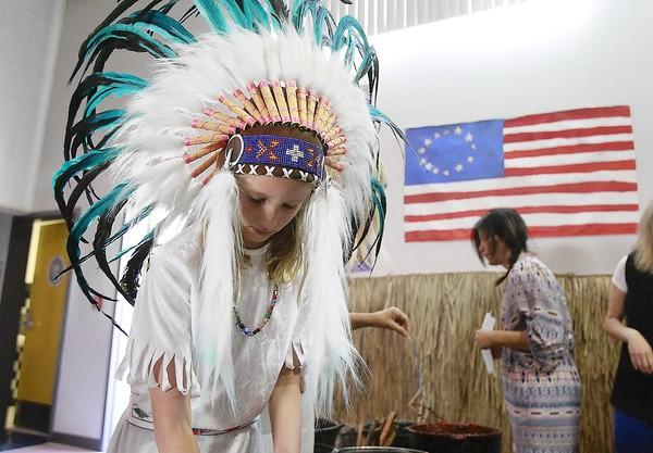 Fourth-grader Isabel Foley, dressed in a native American replica headdress, makes homemade candles during annual El Morro Elementary Colonial Days event during lunch on Monday.