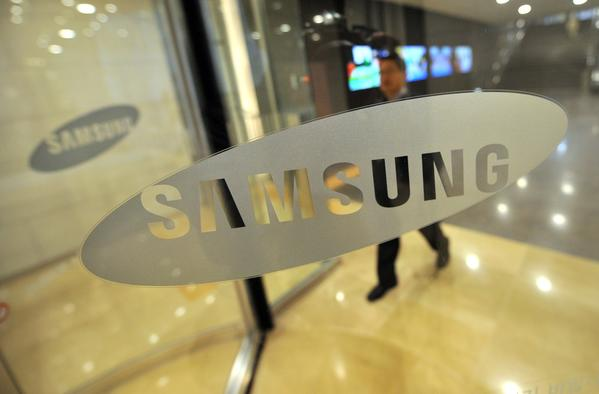 The Samsung logo is displayed on a glass door at its headquarters in Seoul.