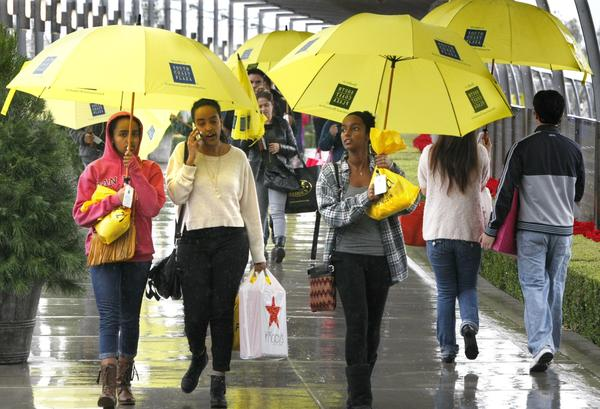 Shoppers armed with borrowed umbrellas and bags of sale items walk through South Coast Plaza on a rainy Black Friday morning.
