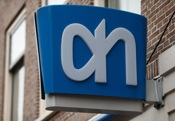 European government bonds were little changed as investors showed a muted reaction to Standard & Poor's decision Friday to raise its outlook on Spain's debt and strip the Netherlands of its top credit rating. Above, a store logo on a sign outside an Albert Heijn supermarket in Utrecht, Netherlands.