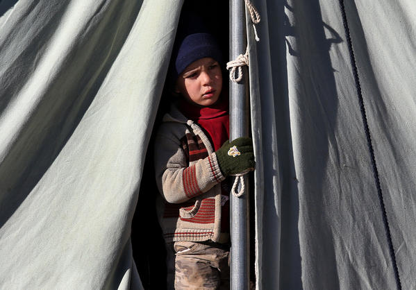 A Syrian child looks out from his tent at a refugee camp in the eastern Lebanese border town of Arsal on Friday.