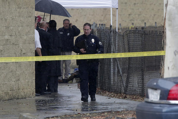 Authorities investigate the 5700 block of Mesmer Avenue, where a burned body was found near a flood channel behind businesses in Playa Vista on Friday.