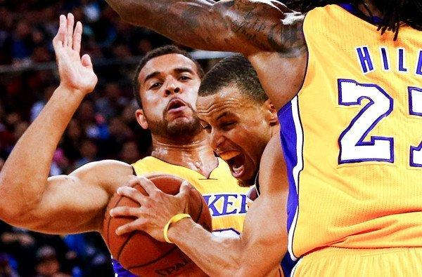 Lakers rookie Elias Harris, left, playing defense against Golden State's Stephen Curry in a preseason game.