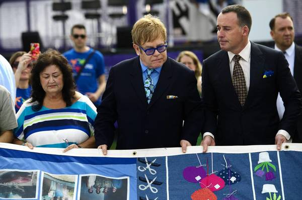 Jeanne White, mother of Ryan White, Elton John, center, and David Furnish with the AIDS Memorial Quilt.