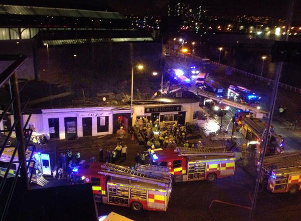 Emergency rescue crews work through the night after a police helicopter crashed through the roof of a crowded pub on the banks of the Clyde River in Glasgow, Scotland, as seen in this cellphone picture sent via Twitter by witness Jan Hollands.
