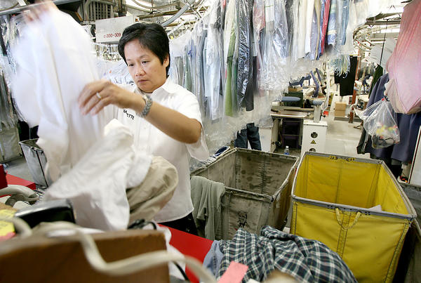File Photo: Nanette Santos sorts through garments waiting to be cleaned at Flair Cleaners in Burbank in July 2009. Flair celebrates 40 years of business in Burbank this year.