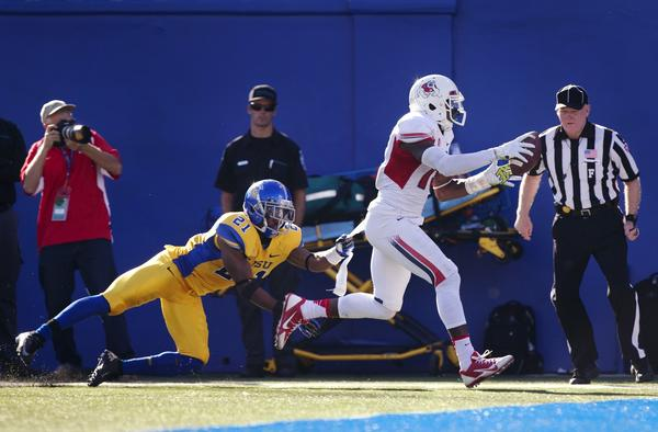 Fresno State wide receiver Davante Adams turns a pass into a touchdown as San Jose State's Bene Benwikere tries to tackle him.