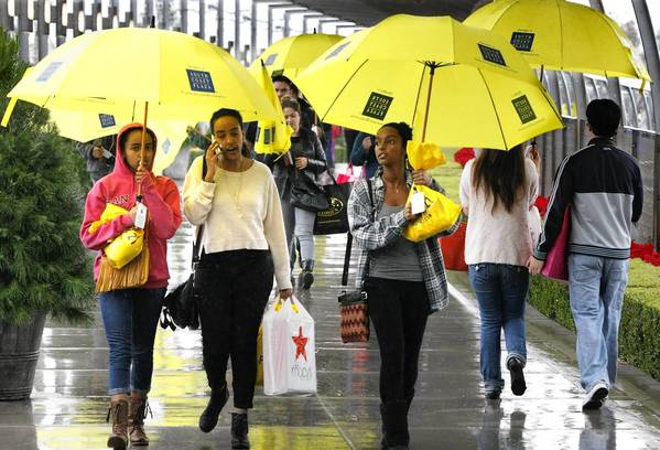 Shoppers at South Coast Plaza in Costa Mesa carry borrowed umbrellas through the rain the morning of Black Friday.