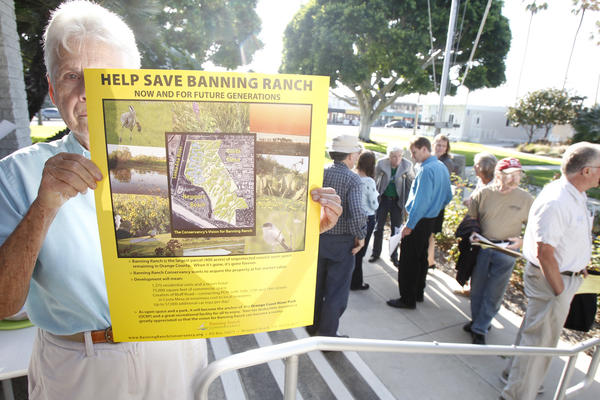 A woman against Banning Ranch development holds up a sign outside the Newport Beach City Council meeting last year.