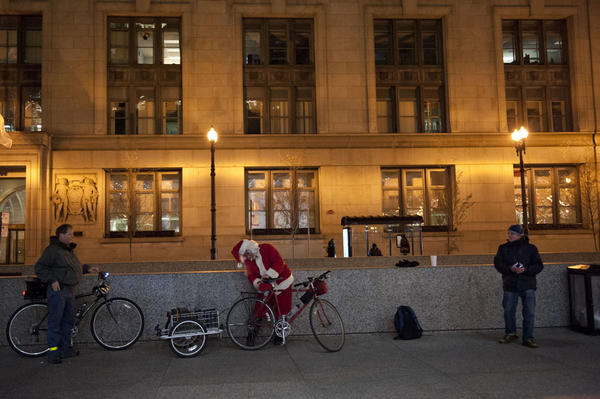 Ken Gray, center, sets up his bike to play music before the Critical Mass ride begins at Daley Plaza (50 W. Washington St.) on Nov. 29. (Rena Naltsas for the RedEye)