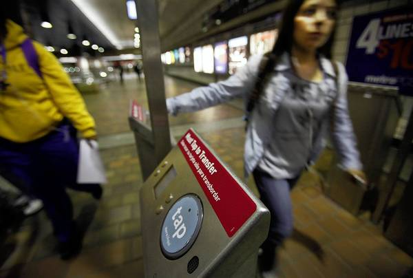 Commuters swipe their TAP (Transit Access Pass) cards at the 7th Street/ Metro Center station in downtown L.A. Officials began locking the subway turnstiles in June, stopping many people from riding for free.