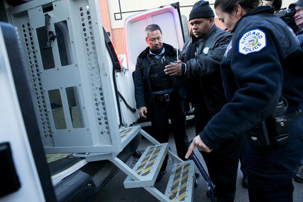 Protester Myron Byrd is arrested and led into a police vehicle after he and others blocked North Broadway Street during a demonstration at a Wal-Mart store on the North Side on Black Friday.