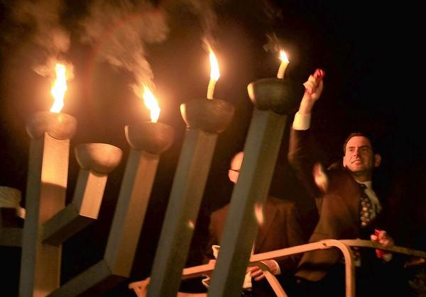 Sr. Rabbi Gersh Zylberman, right, uses fire as he lights up a menorah on the third night of Hanukkah at Temple Bat Yahm in Newport Beach on Friday. (Kevin Chang/ Daily Pilot)