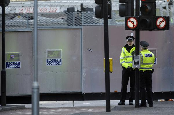 A police barrier walls off the site where a police helicopter crashed through the roof of a pub in Glasgow, Scotland.