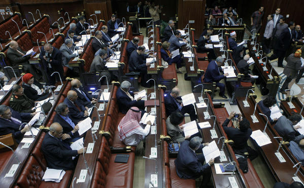 Members of the panel tasked with amending Egypt's constitution read drafts of amendments before they began voting in the Shoura Council in Cairo on Saturday.