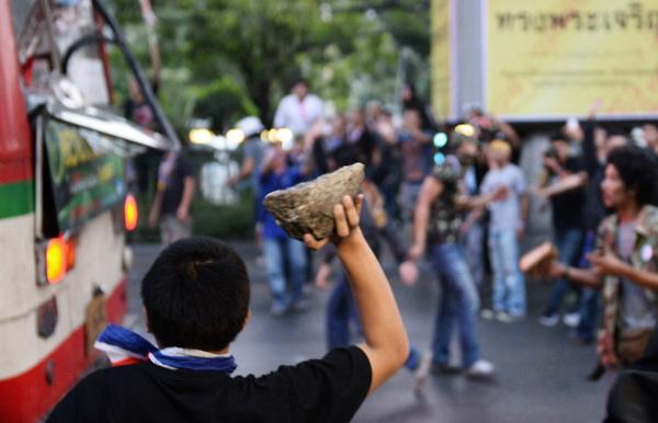 Thai opposition protesters attack a bus carrying pro-government supporters on their way to a rally at a stadium in Bangkok on Saturday.