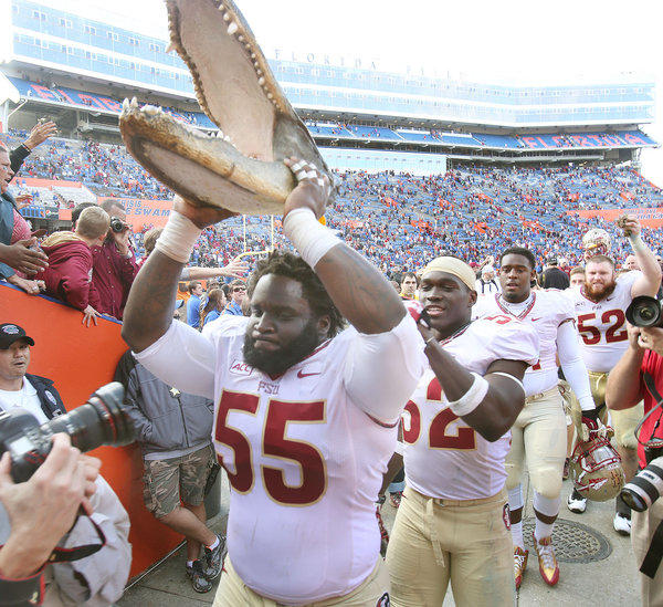 FSU defensive tackle Jacobbi McDaniel (55) holds a gator head aloft as he comes off the field after winning the Florida State at University of Florida football game at Ben Hill Griffin Stadium in Gainesville on Saturday, November 30, 2013. Florida State won the game 37-7. (Stephen M. Dowell/Orlando Sentinel)
