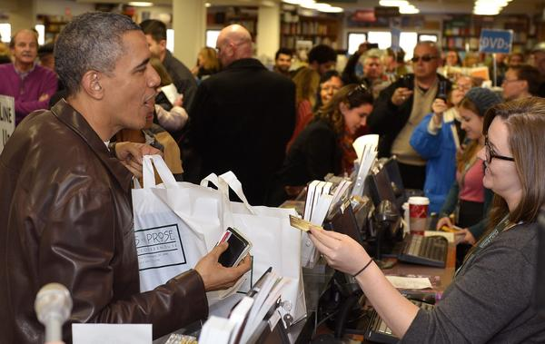 President Obama picks up his purchases as a sales clerk returns his credit card during a shopping trip Saturday to the independent Politics & Prose bookstore in Washington.