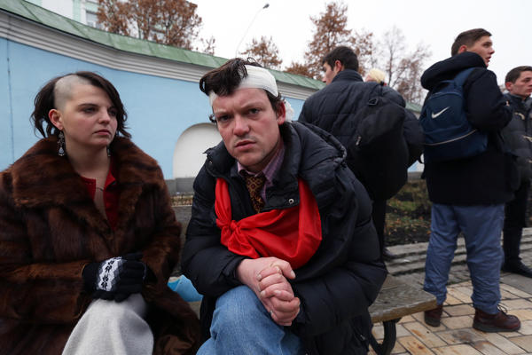 Nelli Didenko and Igor Mitrov sit on the grounds of St. Michael's Cathedral in downtown Kiev on Saturday. Both say they were injured when police used truncheons to clear nearby Independence Square early in the morning.