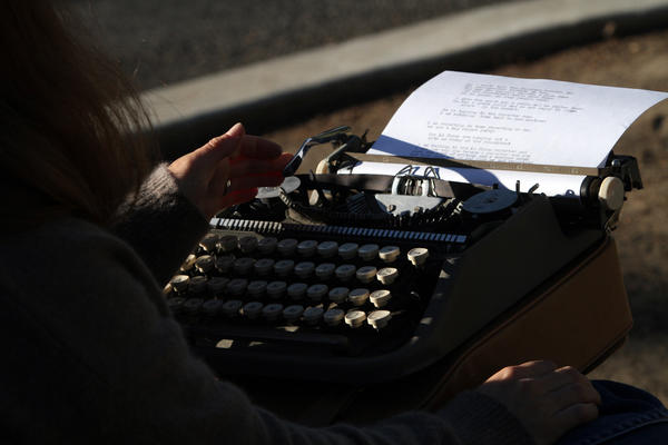 Stacy Dacheux sits at a small green roundabout in Echo Park, typing on her vintage typewriter, recording and becoming part of the daily ritual of people in her neighborhood.