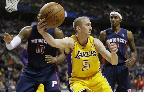 Steve Blake corrals a loose ball and looks to pass around Detroit's Greg Monroe, left, and Brandon Jennings, right, during the Lakers' 106-102 win Friday.