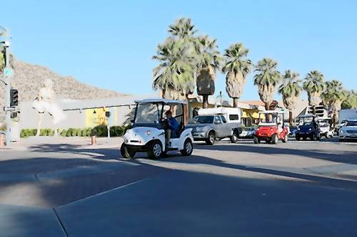Participants in the Drive for Veterans drive through Palm Springs, Calif., in low-speed electric vehicles.