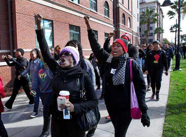 Champagne Ellison, left, a senior at San Jose State University, marches in a protest over reported mistreatment of an African American freshman by his dormitory roommates.