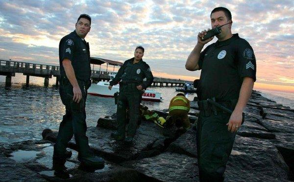 Port of Los Angeles police and emergency officials stand on a Cabrillo Beach breakwater after a man drowned while trying to rescue two others who had been knocked into the water by a wave.