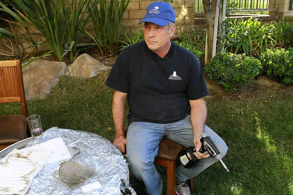 Jim Moseley demonstrates the strength of his ceramic fire shelter with a blowtorch.
