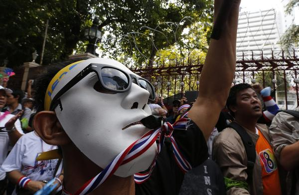 Anti-government protester wearing a mask and blowing a whistle protests outside the Royal Thai Police Headquarters in Bangkok, Thailand, on Sunday.