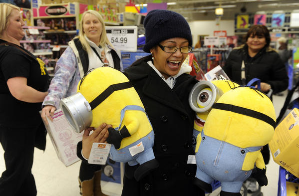 Rollice Roice Abuan of Allentown PA holds three minion dolls from the Despicable Me movie that she is buying at Toys R Us. She and several family members waited in line since 10 this morning in order to get the items they wanted.