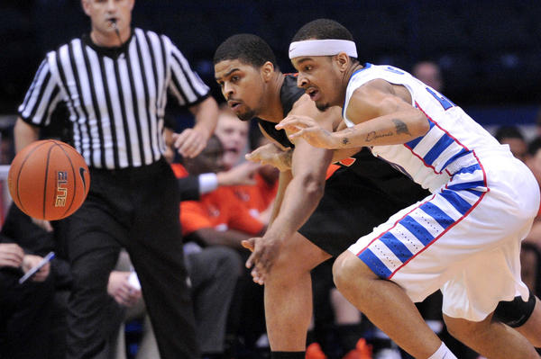 DePaul Blue Demons guard Brandon Young and Oregon State Beavers forward Devon Collier (rear) chase a loose ball during the first half at Allstate Arena.