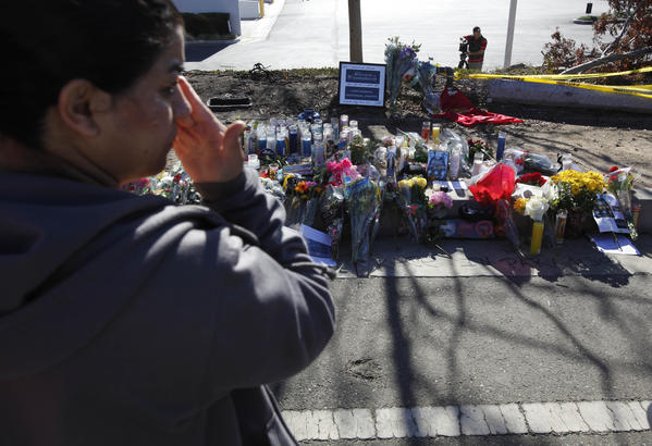 "A woman weeps at a memorial set up near the site where ""Fast & Furious"" actor Paul Walker and a friend were killed Saturday."