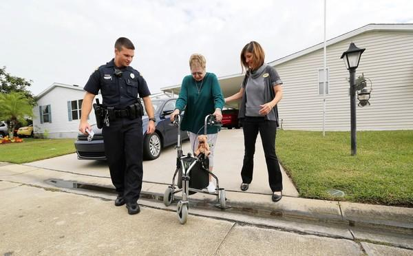 St. Cloud police Officer Ryan Manning and Wilda Belisle of the Osceola Council on Aging help Natalie Craig, 80, outside her home.